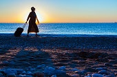Silhouette of Lady walking along Sea Surf pulling Travel Suitcase