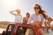 Four Female Friends On Road Trip Standing In Convertible Car