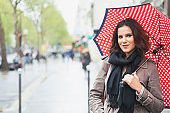 Young woman with umbrella on a street of Paris, France