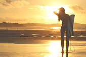 Silhouette of surfer girl at sunset
