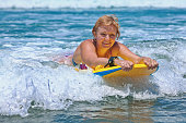 Positive mature woman surfing with fun on ocean waves