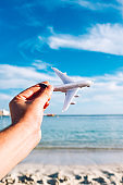 Tourist holds airplane in front of beach and blue sky