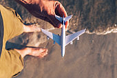 Point of view of tourist holding toy airplane on vacation