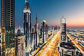 Futuristic architecture of a big city at night. View over the famous highway in Dubai, UAE