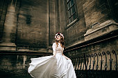 beautiful bride in a wreath and a white wedding dress walking the streets of old European city