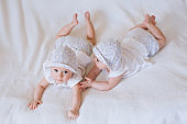 Twin sisters babies lying together . White background
