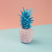 Pink pineapple on pink and blue pastel background. Minimal style