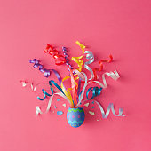 Decorated Easter egg with party streamers on pink background. Easter concept. Flat lay.