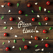 Colorful pizza ingredients pattern made of cherry tomatoes, basil and cheese on wooden background. Cooking concept.