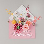 Pink envelope full of various flowers with Happy Mothers day text. Flat lay. Love concept.