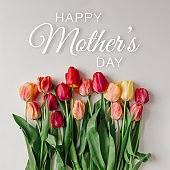 Creative arrangement of tulips on white background with happy Mothers day text. Flat lay.