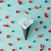 White flower in ice cream cone with forest fruit pattern. Flat lay. Summer concept.