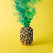 Pineapple with green smoke on bright yellow background. Friut concept.
