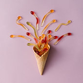 Ice cream cone with gummy candy on pastel pink background. Minimal food concept. Flat lay.