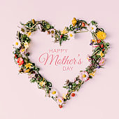 Heart symbol made of flowers and leaves with happy Mothers day text on white background.