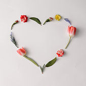 Heart shape made of colorful spring flowers and leaves. Flat lay. Love concept.