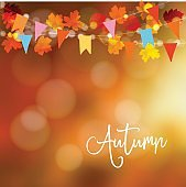 Autumn, fall background. Greeting card with maple and oak leaves and bokeh lights. String decoration with colorful party flags. Modern blurred vector illustration