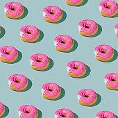 Pink glazed donut pattern on blue pastel background. Creative concept.