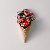 Ice cream cone with colorful flowers on white background. Flat lay. Minimal summer concept.