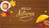 Hello Autumn banner on wooden background.