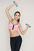 Fitness model woman with dumbbells on white