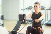 Woman exercising on rowing machine in gym.