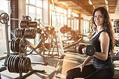 Young athletic woman pumping up muscles with dumbbells.