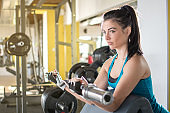 Young beautiful woman doing biceps curl with EZ curl bar in a gym.
