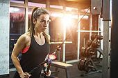 Fitness woman exercising on pull down machine at gym.