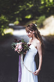 Portrait of bride close up with wedding bouquet with silk ribbons
