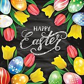 Happy Easter on black chalkboard background with eggs and tulips
