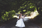 Portrait of happy bride on country road at summer. Wedding bouquet with silk ribbons. She whirls in dance