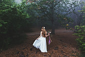 Bride whirls in light dress in the beautiful fairy forest. Foggy autumn weather