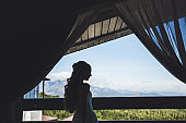 Bride's silhouette in window with beautiful mountain view in summer