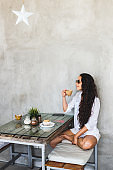 Young brunette woman drink coffee in modern loft cafe with cement walls and textured wooden table. Happy and smile, breakfast with muffin