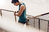 Male runner checking progress on smart watch