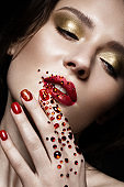 Beautiful girl with evening make-up, red lips in rhinestones and design manicure nails. beauty face.
