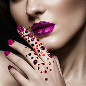 Beautiful girl with evening make-up, purple lips in rhinestones and design manicure nails. beauty face. Close up
