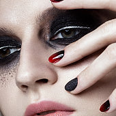 Beautiful blond girl with dark smokey makeup and art manicure design nails. beauty face.