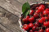 Sweet fresh cherries in basket on wood