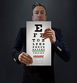 Doctor Holding Snellen Chart