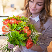 Flower delivery to the office. Young happy woman holding beautiful bouquet