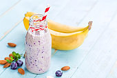 Banana and blueberry diet smoothie with yogurt or milk, almonds and fresh berries in glass bottles, healthy food