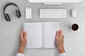 Knolling office desk hands holding notebook