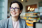 Smiling Businesswoman Enjoying Break in Cafe