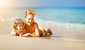 Happy family mother and chid daughter in masks on beach in summer
