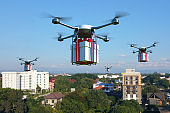 Drone with white gift box flying over the town.