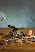 The silver and golden coins and falling coins on wooden background