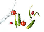 The fresh tomatos, cucumbers, radish in spray of water