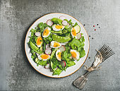Healthy spring green salad with vegetables, pea and boiled egg
